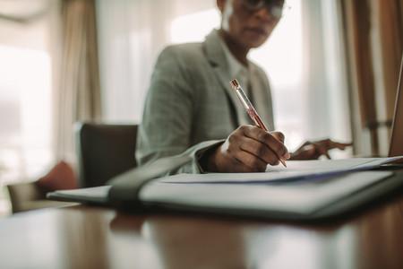 Female at hotel room desk making notes