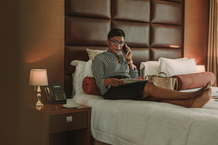 Businesswoman in hotel room with newspaper talking over phone