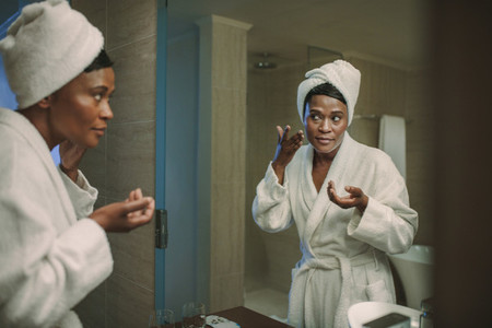 African woman taking care of her skin in bathroom