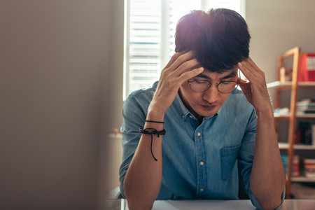 Man at his desk looking stressed and tired