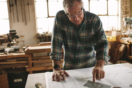 Carpenter studies the construction plan in his workshop