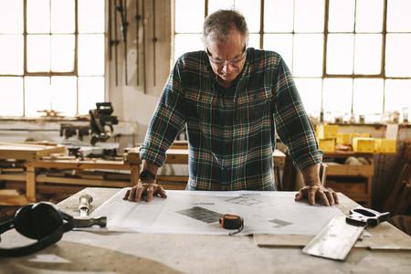 Senior carpenter checking drawing in workshop