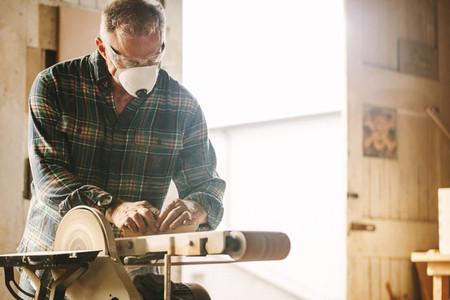 Senior carpenter with mask using belt sander