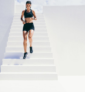 Fitness woman doing workout running down the stairs