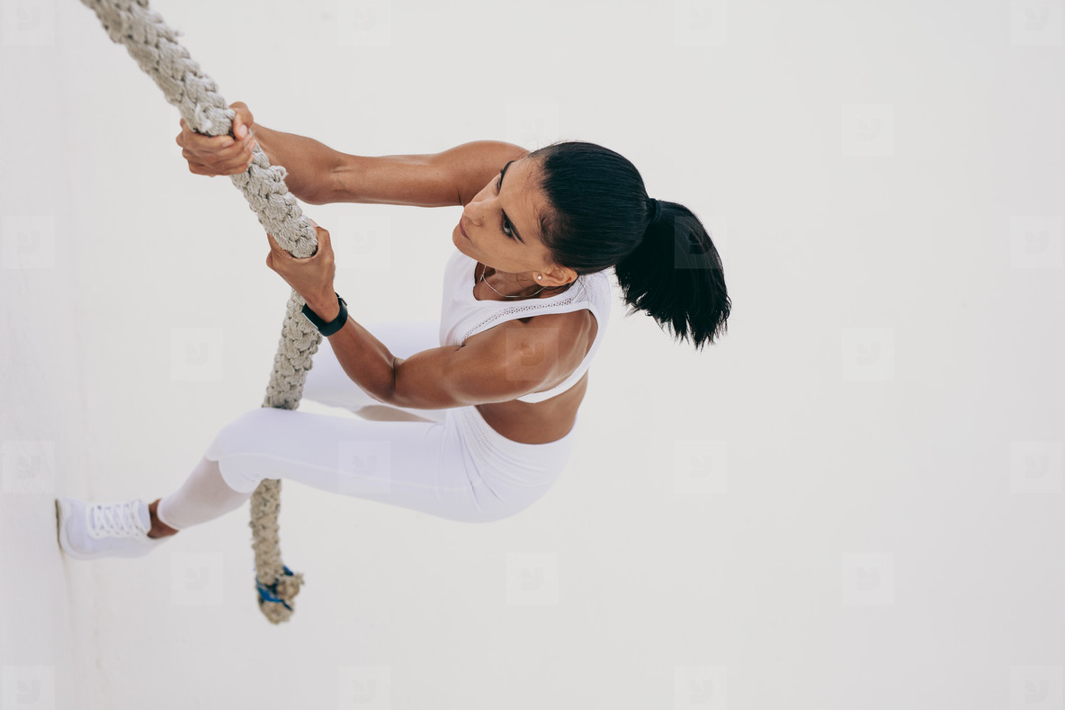 Fitness woman climbing a wall using a rope