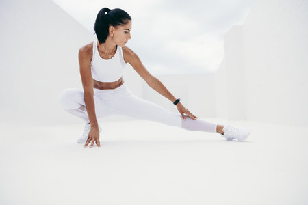 Fitness woman doing leg stretches