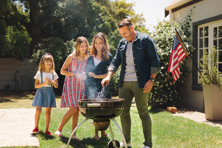 Couple standing with their kids in their backyard making barbequ