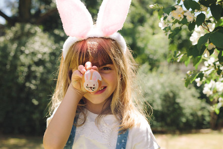 Portrait of a little girl showing a painted easter egg