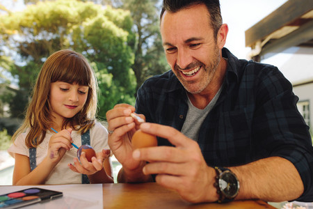 Father and daughter putting paint on easter eggs