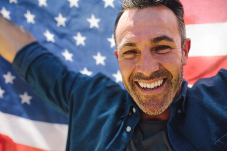 Close up of a smiling man holding american flag behind him