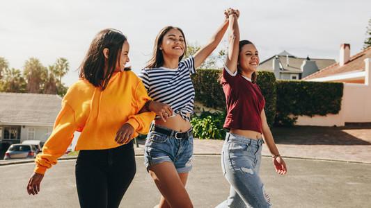 Happy teenage girls walking on street