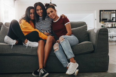 Girl friends sitting on couch holding each other