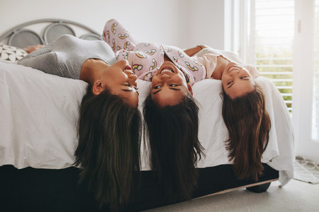 Girls lying on bed having fun at a sleepover