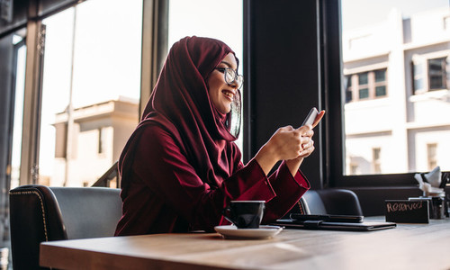 Woman in hijab sitting at cafe using mobile phone
