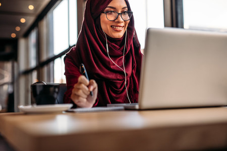 Muslim woman having video chat at cafe