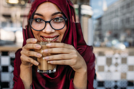 Smiling woman hijab having coffee at cafe