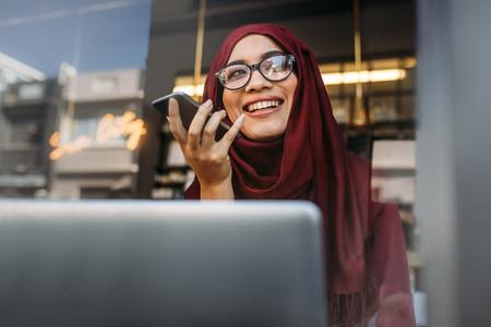 Muslim woman running business online from coffee shop