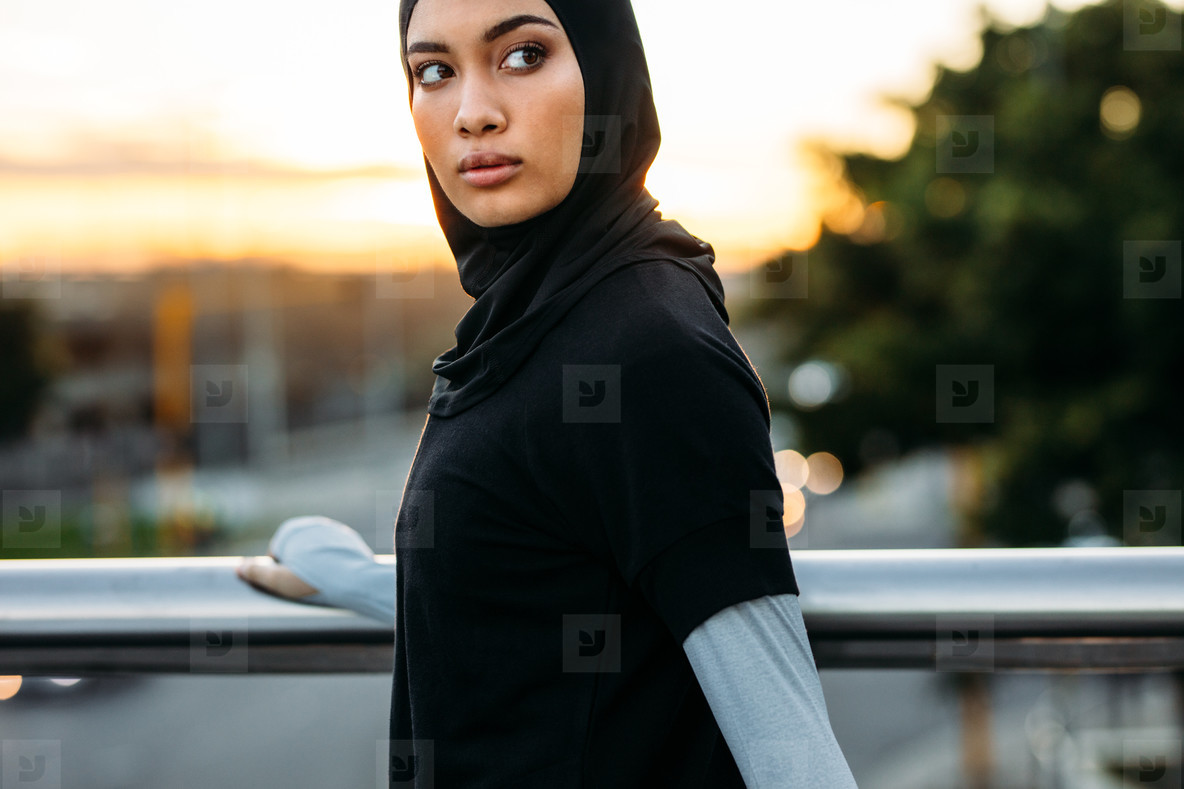 Fitness woman in hijab standing outdoors in morning