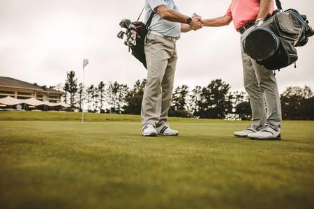Senior golfers handshake at the golf course