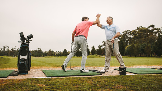 Senior golfers high five at driving range