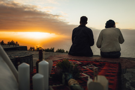 Couple having picnic looking at sunset