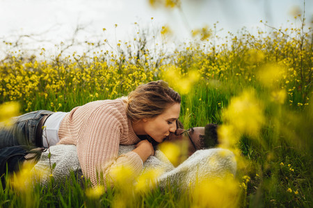 Romantic couple kissing on flowering meadow
