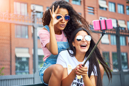 Laughing young friends making faces and taking selfies together outside