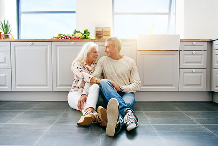 Affectionate senior couple sitting together on their kitchen floor