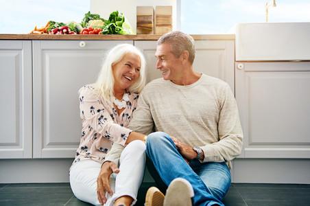Elderly couple chatting on a kitchen floor