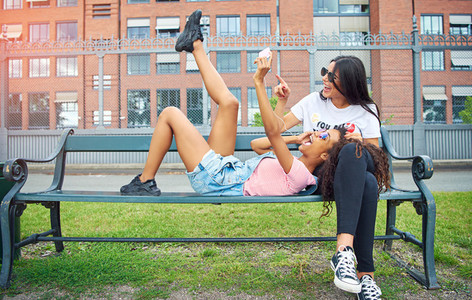 Carefree young girlfriends sitting on a bench outside taking selfies