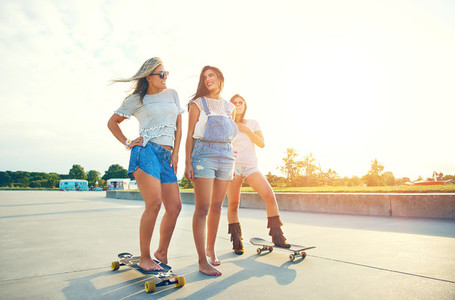 Three young female friends skateboarding against sunset