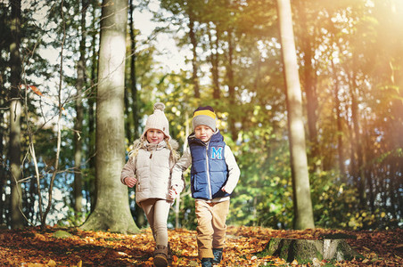 Two happy children walking through the forest