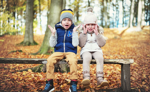 Two sitting children with their hands up