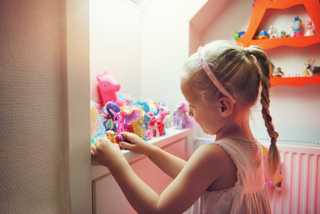 Girl playing with figurines in her room