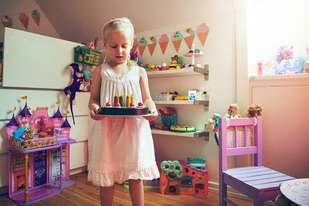 Adorable little girl standing with toy cake