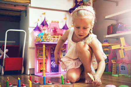 Cute little girl with sliced toy cake