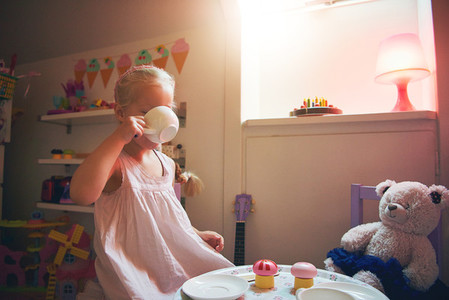 Girl drinking tea with her toy bear