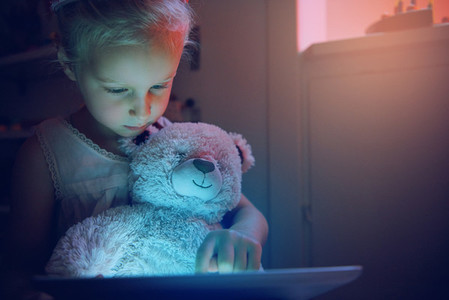Girl using tablet pc while holding bear