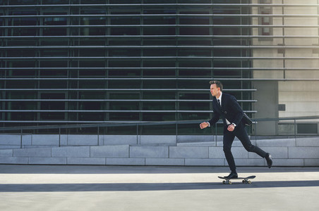 Businessman pushing his skateboard with purpose