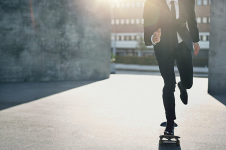 Unrecognizable man in suit riding a skateboard
