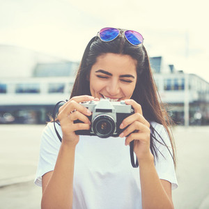 Laughing young woman checking the viewfinder