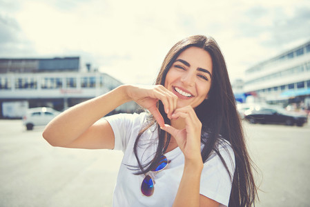 Laughing young woman making a heart gesture