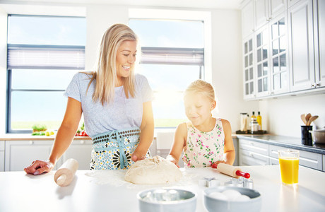 Mother and daughter baking in a white kitchen