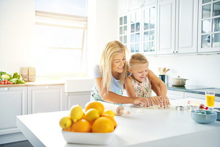 Young mother and daughter baking together