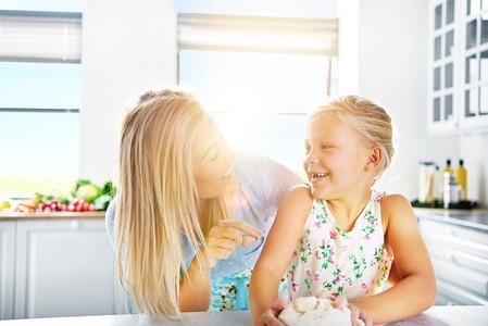 Loving mother teaching her daughter to bake