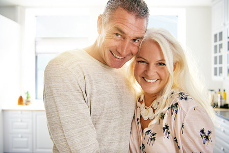 Joyful middle aged man and woman indoors