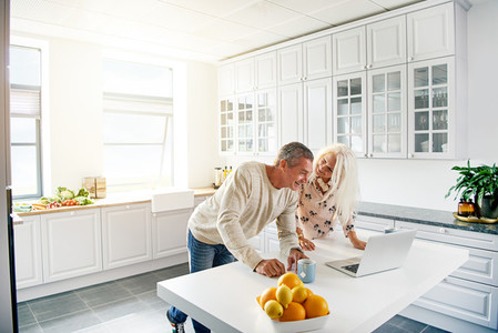 Kitchen scene with couple looking at computer