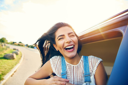Cheerful young woman with brown hair in car