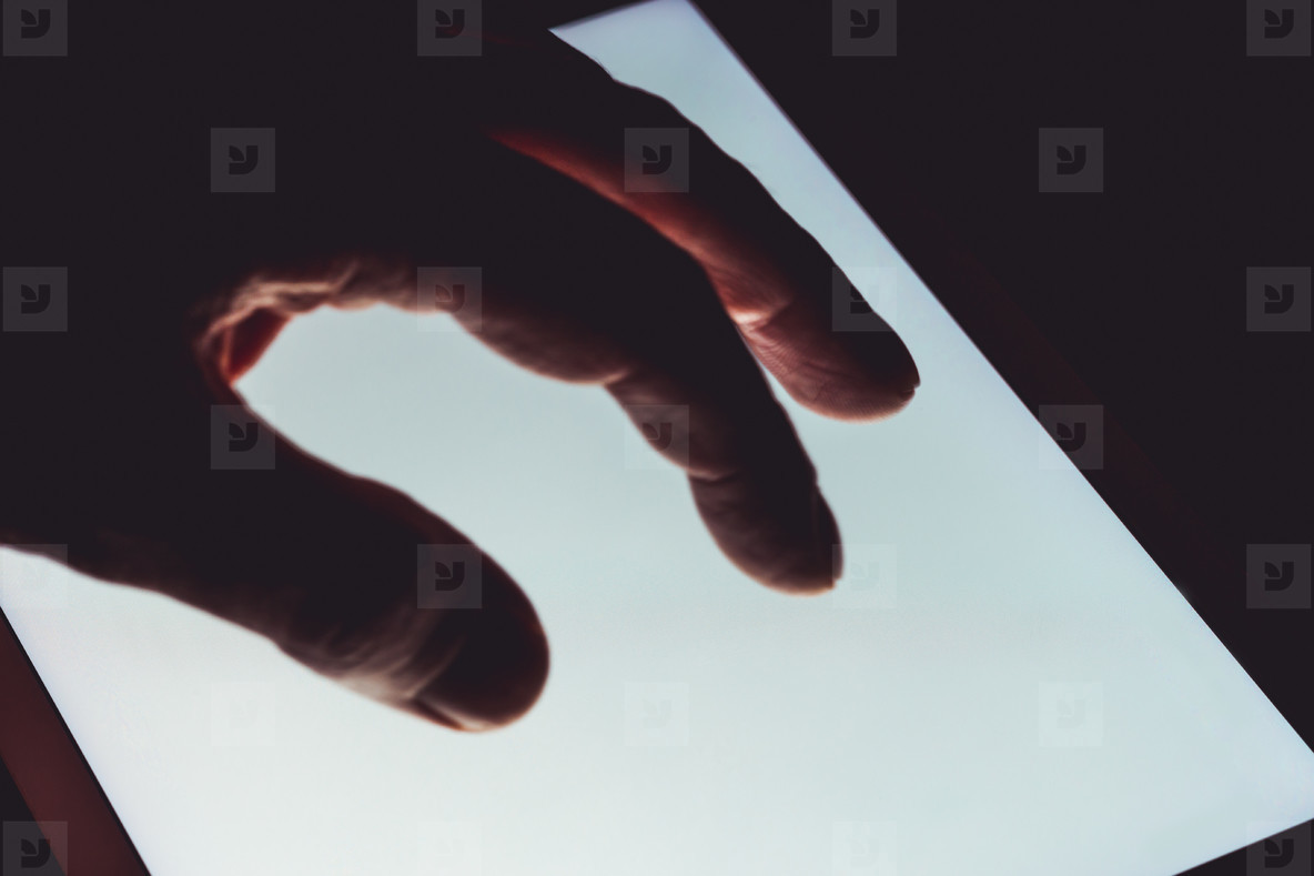 Hand using touch screen tablet business computer night