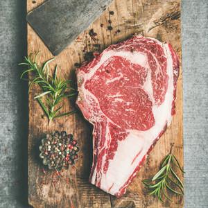 Raw prime beef meat steak rib eye and chopping knife flat lay